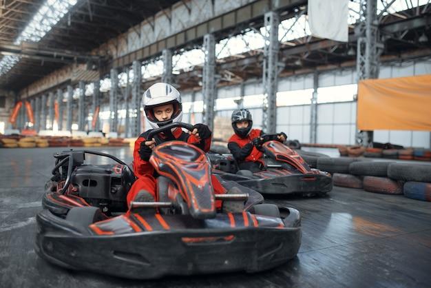 Zwei kart-rennfahrer betreten die kurve, vorderansicht, kart-autosport indoor.