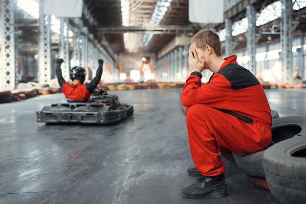 Zwei kart-rennfahrer, sieger und verlierer, kart-autosport in der halle.
