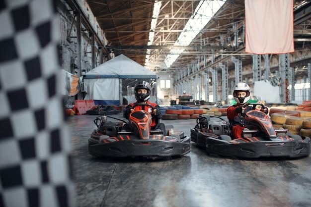Zwei kartrennfahrer an der startlinie, zielflagge
