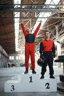 Zwei kartrennfahrer auf dem podium, sieger, kart-autosport in der halle.