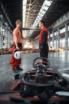 Zwei kartrennfahrer in ausrüstung, kartsport in der halle.