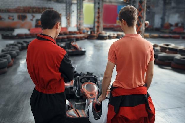 Zwei kartrennfahrer in ausrüstung, kartsport
