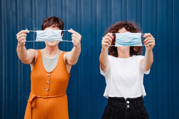 Zwei kaukasische frauen, die draußen gesichtsmaskengruß mit ellbogen halten. pandemie während des konzepts der sozialen distanz des corona-virus.