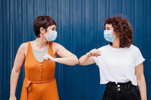 Zwei kaukasische frauen im freien tragen gesichtsmaske gruß mit ellbogen. pandemie während des konzepts der sozialen distanz des corona-virus.