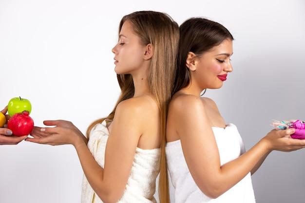 Zwei kaukasische frauen legen wert auf einen gesunden lebensstil und die andere auf kosmetik