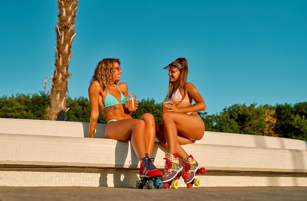 Zwei kaukasische freundinnen in badeanzügen trinken saft oder limonade und rollerblade in strandnähe.