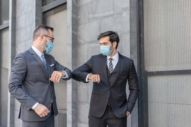 Zwei kaukasische geschäftsleute tragen eine medizinische maskenbegrüßung mit stoßenden ellbogen während der covid-19-epidemie des coronavirus auf der straße