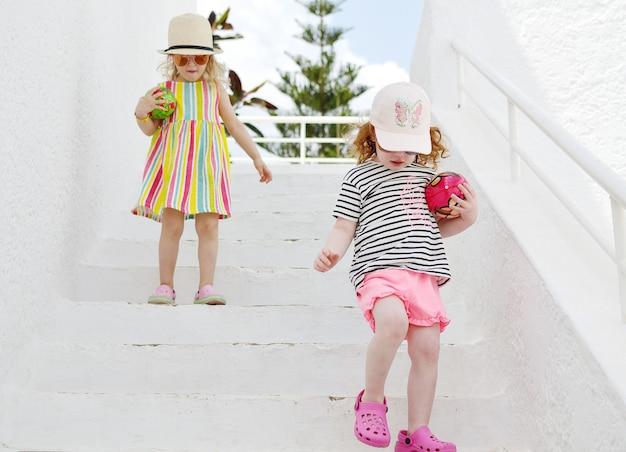 Zwei kaukasische kleine blonde mädchen, die mit sommerkleidung gehen