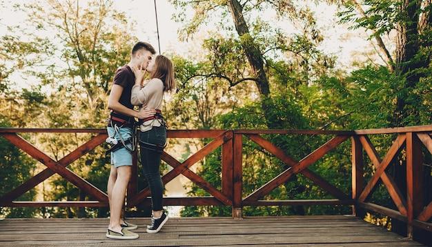 Zwei kaukasische liebhaber küssen sich, bevor sie eine große portion positiver emotionen auf einer tiroler traverse bekommen