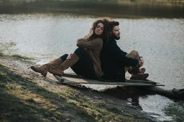 Zwei kaukasische liebhaber sitzen auf dem pier am see. ein bärtiger mann und eine verliebte lockige frau. valentinstag.