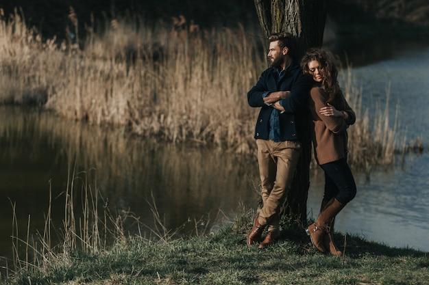 Zwei kaukasische liebhaber stehen in der nähe eines baumes am see. ein bärtiger mann und eine verliebte lockige frau. valentinstag.