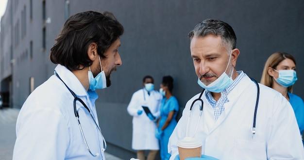 Zwei kaukasische männer, ärztekollegen reden und trinken kaffee zum mitnehmen. männliche ärzte diskutieren über arbeit und nippen an einem heißen getränk. kommunikation von medizinern. gespräch im krankenhaus.