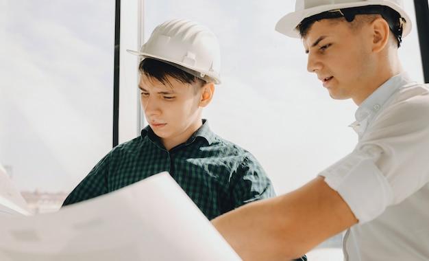 Zwei kaukasische männer mit helm planen ein gebäude auf einem großen papier
