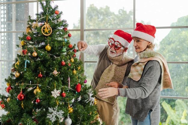 Zwei kaukasische seniorenpaare mit pullover und weihnachtsmütze schmücken den weihnachtsbaum zusammen in der nähe des fensters in der weihnachts- und neujahrsfestfeier zu hause im winter. aktivitäten zu weihnachten und neujahr.