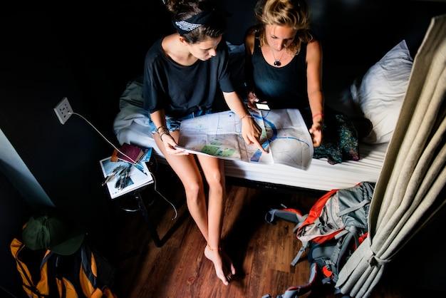 Zwei kaukasische touristen, die auf dem bett betrachtet die karte sitzen