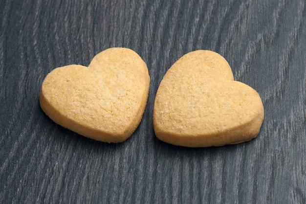 Zwei kekse in herzform auf einem dunklen holzbrett