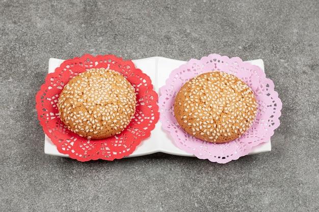 Zwei kekse mit sesam auf weißer untertasse