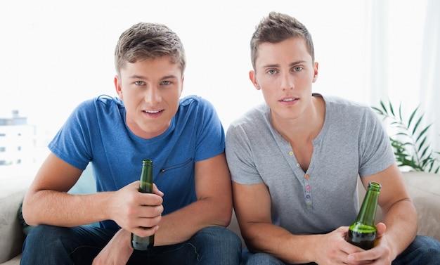Zwei kerle, die in der hand die kamera mit bier untersuchen