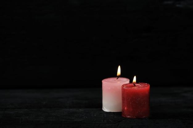 Zwei kerzen mit beleuchtetem feuer auf schwarzem hintergrund