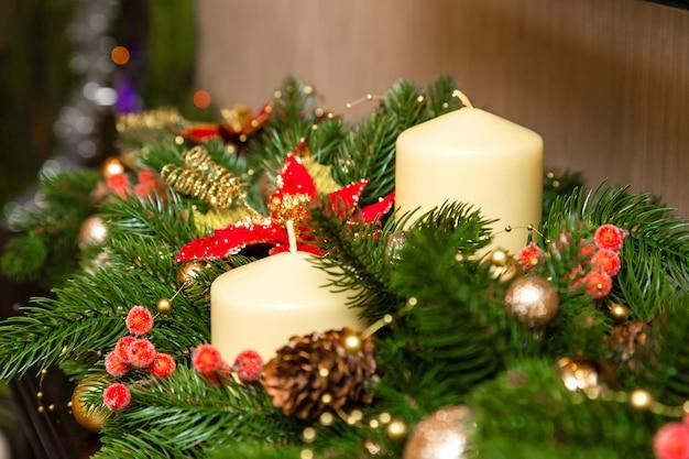 Zwei kerzen mit dekoration des weihnachtsbaumes