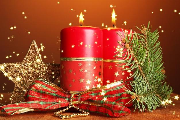 Zwei kerzen und weihnachtsschmuck, auf braunem hintergrund