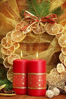 Zwei kerzen und weihnachtsschmuck auf goldener oberfläche