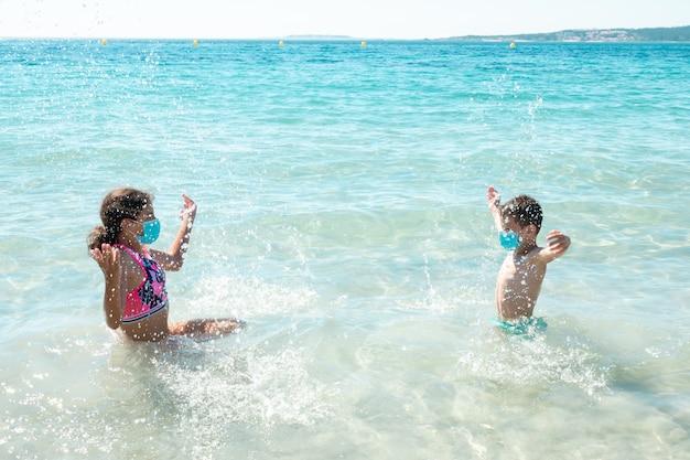 Zwei kinder am strand tragen schutzmasken gegen coronavirus