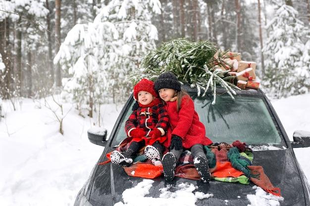 Zwei kinder auf der motorhaube eines autos neben einem weihnachtsbaum und geschenken