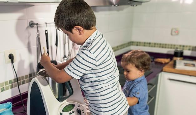 Zwei kinder backen kuchen zu hause.