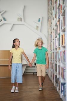 Zwei kinder beeindruckt von einer vielzahl von büchern in den regalen