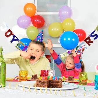 Zwei kinder bei großer geburtstagsfeier