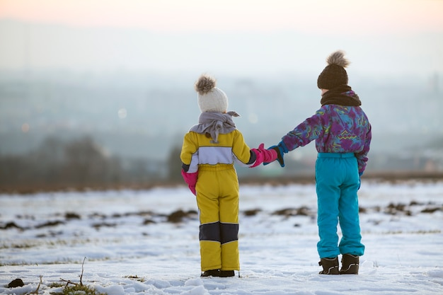 Zwei kinder bruder und schwester stehen im freien auf schneebedeckten winterfeld händchen haltend.
