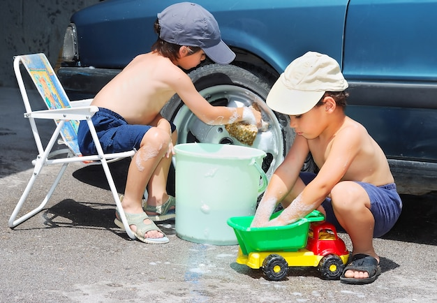 Zwei kinder, die auto und spielzeugauto besiegen