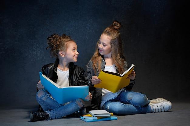 Zwei kinder, die das buch im grauen studio lesen