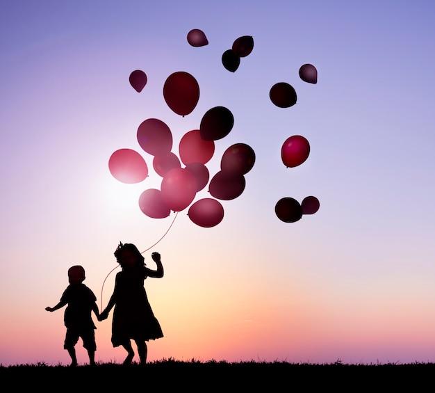 Zwei kinder, die im freien ballone zusammenhalten