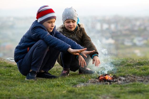 Zwei kinder, die im freien bei kaltem wetter mit feuer spielen
