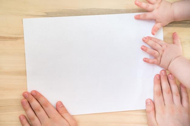 Zwei kinder, die leeres papier auf hölzernem hintergrund halten. platz für ihren text.