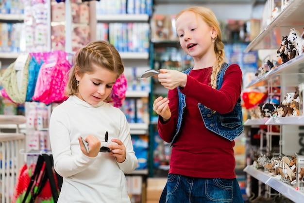 Zwei kinder, die spielwaren im spielzeugsladen kaufen