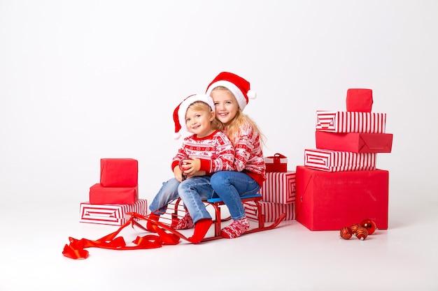 Zwei kinder, ein junge und ein mädchen in pullovern und hüten santa, sitzen auf einem schlitten, um geschenke zu tragen. studio, weißer hintergrund, platz für text