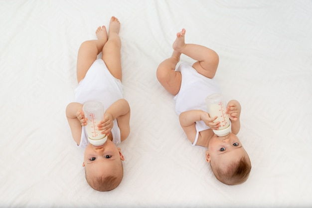 Zwei kinder, ein junge und ein mädchen, zwillinge von 8 monaten, trinken milch aus einer flasche auf dem bett im kinderzimmer und füttern das baby, babynahrungskonzept, draufsicht