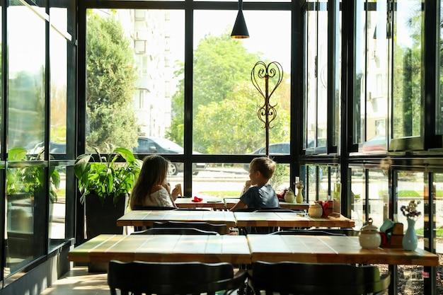 Zwei kinder essen im restaurant eis