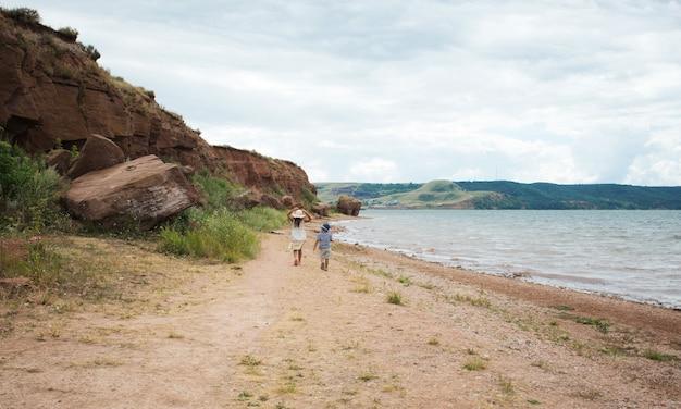Zwei kinder gehen ans meer. große schwester und bruder