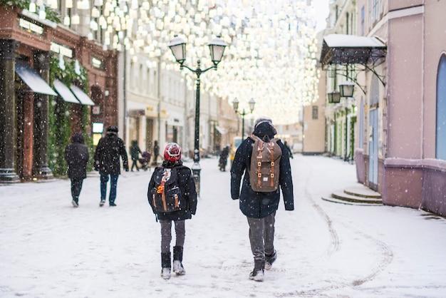 Zwei kinder gehen in der wintersaison unter schneefall durch die straßen der stadt