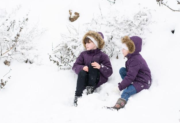 Zwei kinder in lila jacken sitzen in der nähe von schneebedeckten büschen