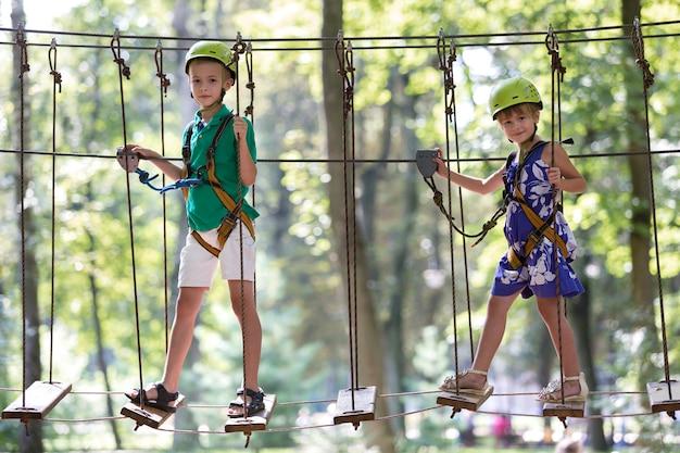 Zwei kinder, junge und mädchen im schutzgurt und schutzhelme beim klettern auf seilbahn.