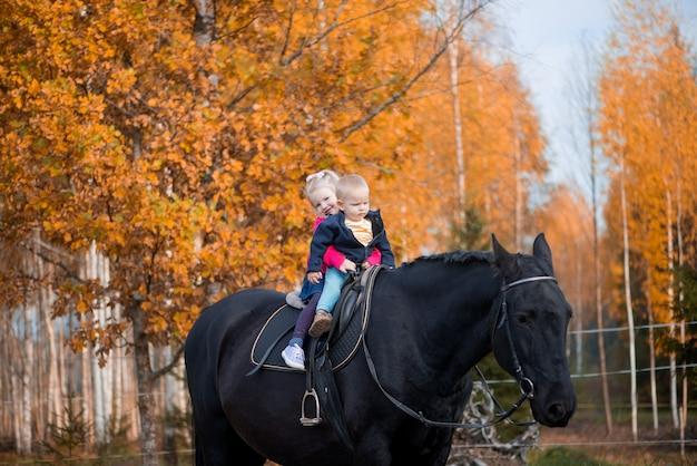 Zwei kinder jungen und mädchen, die auf einem schwarzen pferd reiten, haben glückliche lustige gefühle