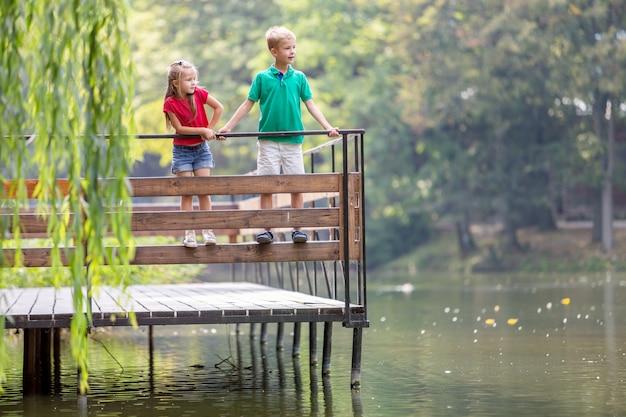Zwei kinder jungen und mädchen stehen auf holzdeck an einem seeufer.
