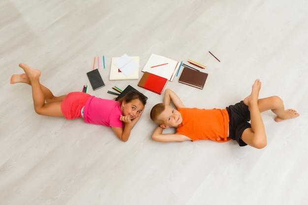 Zwei kinder, kleine mädchen des vorschulalters, die zu hause tablette auf dem boden aufpassen