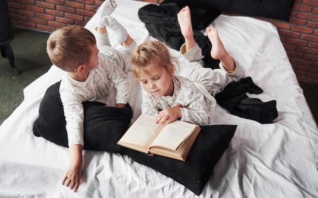 Zwei kinder liegen auf einem großen bett und lesen ein interessantes buch. sie tragen den gleichen pyjama
