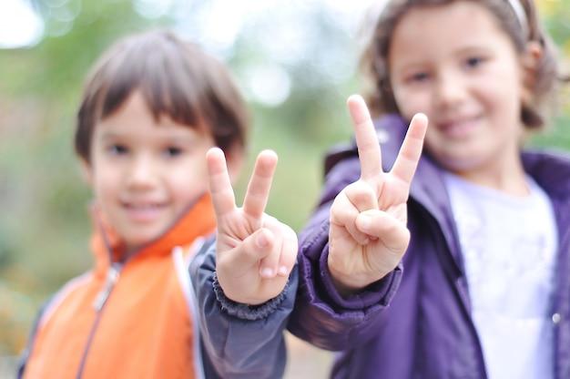 Zwei kinder, männlich und weiblich mit den siegfingern